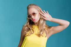 Stående av den härliga blonda kvinnan i solglasögon och gul skjorta på blå bakgrund carefree sommar fotografering för bildbyråer