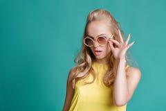 Stående av den härliga blonda kvinnan i solglasögon och gul skjorta på turkosbakgrund carefree sommar arkivfoton