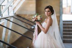 Stående av den härliga bruden med bukettblommor i den vita lyxiga klänningen Ursnygg modell med brud- makeup och frisyren arkivfoto