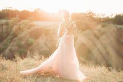 Stående av den härliga bruden med buketten av blommor arkivfoton