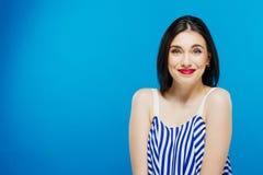 Stående av den härliga brunetten i den randiga sommarklänningen som poserar i studio på blå bakgrund Royaltyfri Bild