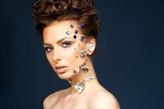 Stående av den härliga brunetten med diamanter på henne framsida Arkivbild