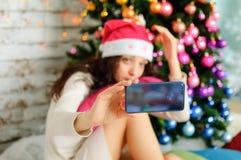 Stående av den härliga brunetten med långt mörkt hår i den rosa Santa Hat Photographing Herself Using grejen nära jul royaltyfri foto
