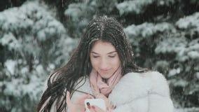 Stående av den härliga brunettflickan som talar vid telefonen i snöig vintertid lager videofilmer