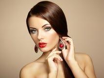Stående av den härliga brunettkvinnan med örhänget. Perfekt makeu Arkivbilder