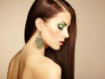 Stående av den härliga brunettkvinnan med örhänget. Perfekt makeu Fotografering för Bildbyråer