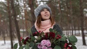 Stående av den härliga caucasial asiatiska flickan för blandat lopp som rymmer en bukett av blommor i snöig pinjeskog för vinter  arkivfilmer