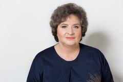 Stående av den härliga eleganta kvinnan i en välskött äldre srudii på en vit bakgrund med makeup och utan makeup Arkivfoton