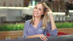 Stående av den härliga europeiska le affärskvinnan som ser kameran och spelar med hennes hår stock video