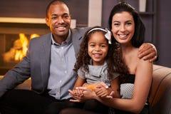 Stående av den härliga familjen för blandad race hemma royaltyfri foto