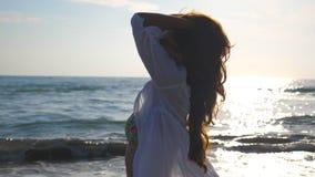 Stående av den härliga flickan i bikini och skjorta som promenerar kusten och spelar med hennes hår Lycklig ung kvinna in lager videofilmer