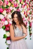 Stående av den härliga flickan i klänning över färgrik blommabackgr royaltyfria bilder