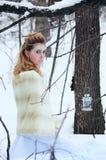 Stående av den härliga flickan i vinterskogen Arkivbild