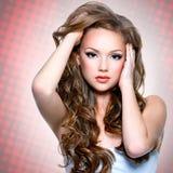 Stående av den härliga flickan med långa lockiga hår Arkivfoto