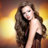 Stående av den härliga flickan med långa lockiga hår royaltyfri foto
