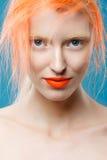 Stående av den härliga flickan med orange hår på en blå bakgrund Arkivfoto