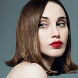 Stående av den härliga flickan med röd läppstift i studion på en grå bakgrund Royaltyfria Foton
