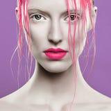 Stående av den härliga flickan med rosa hår på en vit bakgrund Fotografering för Bildbyråer