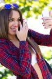 Stående av den härliga flickan som använder hennes mobiltelefon i stad Arkivbild