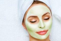 Stående av den härliga flickan som applicerar den ansikts- maskeringen arkivfoto