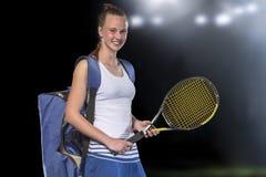 Stående av den härliga flickatennisspelaren med en racket på mörk bakgrund arkivfoto