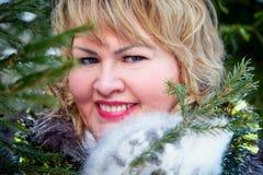 Stående av den härliga fylliga kvinnan i en trevlig vinterskog arkivbilder