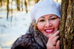 Stående av den härliga fylliga kvinnan i en trevlig vinterskog arkivfoto