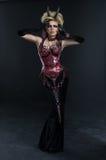 Stående av den härliga jäkelkvinnan i mörk sexig klänning royaltyfri bild