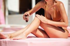 Stående av den härliga kvinnakroppen i bikinisammanträde på strandsäng Flaska för kropp för hand för ung kvinna hållande olje- oc arkivfoton