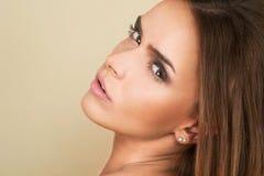 Stående av den härliga kvinnan för mörkt hår på brun bakgrund Royaltyfri Foto