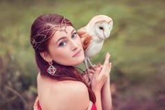 Stående av den härliga kvinnan i diadem med ugglan på hennes hand royaltyfri fotografi