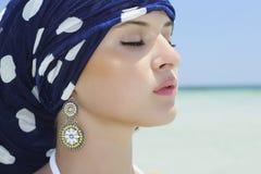Stående av den härliga kvinnan i en blå sjal på stranden. arabisk stil arkivbild