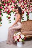 Stående av den härliga kvinnan i klänningen som sitter på tappningsoffaove royaltyfri fotografi