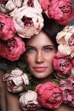 Stående av den härliga kvinnan med blommor runt om henne framsida royaltyfria bilder
