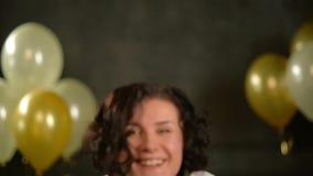 Stående av den härliga kvinnan med kort svart lockigt hår som blåser på guld- konfettier Skämtsamt bära för partiflicka stock video