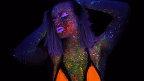 Stående av den härliga kvinnan med purpurfärgad hårdans i UV ljus för neon Modell Girl med fluorescerande idérikt psykedeliskt lager videofilmer