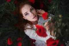 Stående av den härliga kvinnan med rött hår och fräknar i ett vallmofält arkivbild