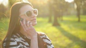 Stående av den härliga kvinnan med Smartphone utomhus Att le brunett med lång hår och Fashional solglasögon är lager videofilmer