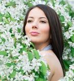 Stående av den härliga kvinnan nära ett blomningträd Arkivbild
