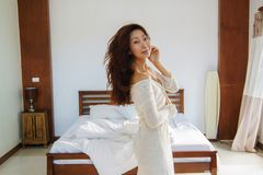 Stående av den härliga kvinnan på säng i sovrummet fotografering för bildbyråer