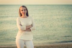 Stående av den härliga kvinnan på solnedgången på kusten Arkivbilder