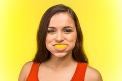 Stående av den härliga kvinnan som äter den nya citronen Fotografering för Bildbyråer