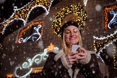 Stående av den härliga kvinnan som framme använder den smarta telefonen av huset royaltyfria bilder