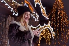 Stående av den härliga kvinnan som framme använder den smarta telefonen av huset royaltyfri bild