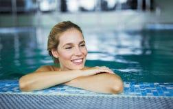 Stående av den härliga kvinnan som kopplar av i simbassäng arkivfoto