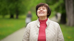 Stående av den härliga kvinnan som ler och tycker om våren i parkera Bärande vitt omslag för attraktiv brunett och stock video