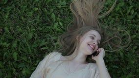 Stående av den härliga kvinnan som ligger på grönt gräs med telefonen arkivfilmer
