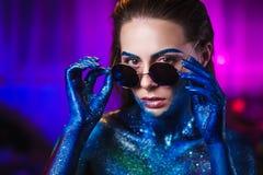 Stående av den härliga kvinnan som målas med kosmiska färger och spangleds Arkivfoto