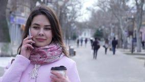 Stående av den härliga kvinnan som omkring talar på mobiltelefonen och blickar, medan gå runt om stad stock video