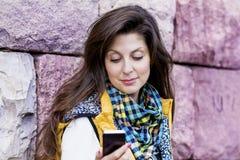 Stående av den härliga kvinnan som talar på den utomhus- telefonen Arkivbilder